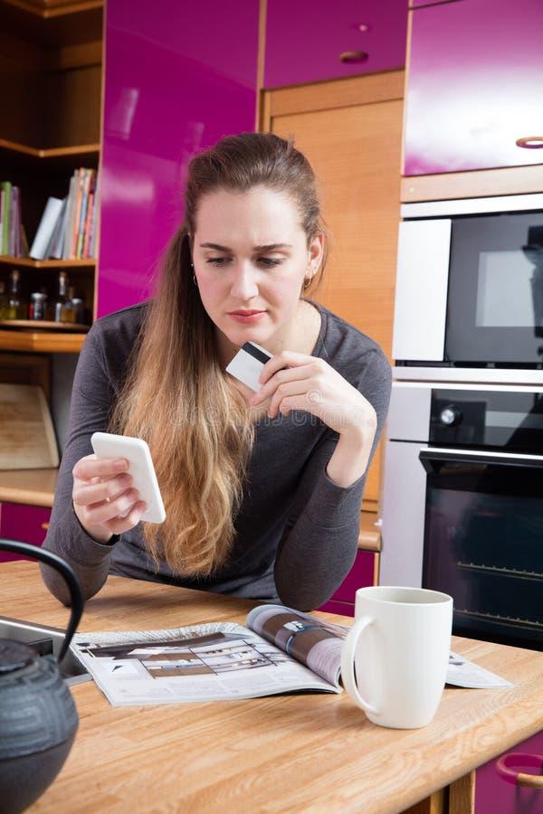 Dubieuze mooie jonge vrouw die online van haar huiskeuken winkelen stock afbeelding