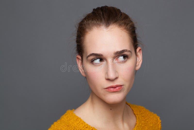 Dubita bella ragazza che guarda in alto, ascolta, osserva emozioni, riprese in studio fotografia stock libera da diritti