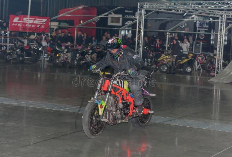 Dublê que monta uma motocicleta durante a mostra do conluio imagens de stock royalty free