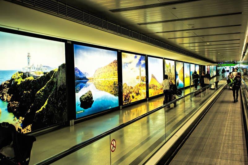 Dublin Airport folk, passagerare som reser med resväskor på gångbanarulltrappan i rörelse med markerade bilder av Irland i t royaltyfri fotografi