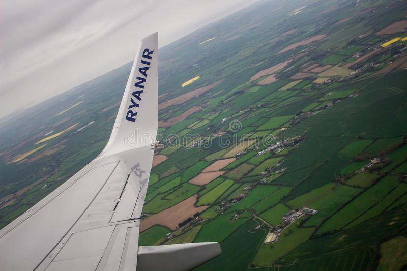 DUBLIN, IRELAND - APRIL 23, 2017: Ryanair logo in the wing of the airplane with sky as the background. Ryanair has cheap flights stock photography
