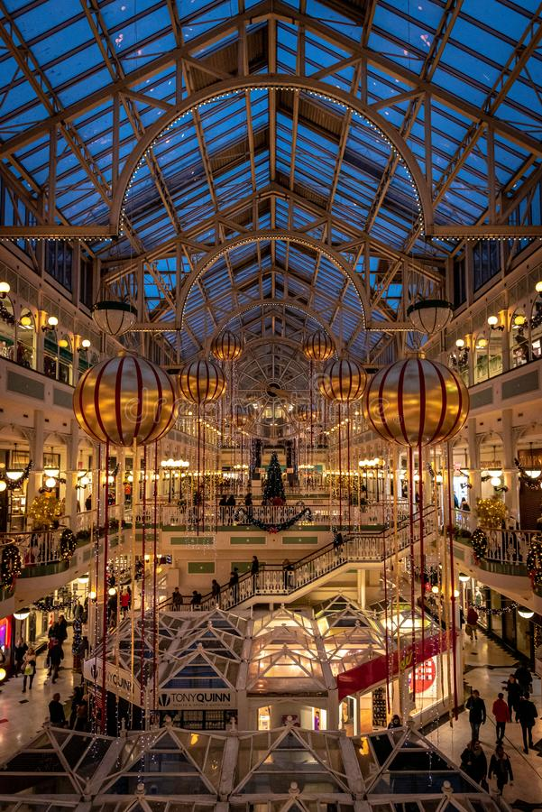 DUBLIN, IRELAND, DECEMBER 24, 2018: People shopping at Stephens Green Shopping Centre, decorated with Christmas lights, balls and. Wreaths, mall, store stock image