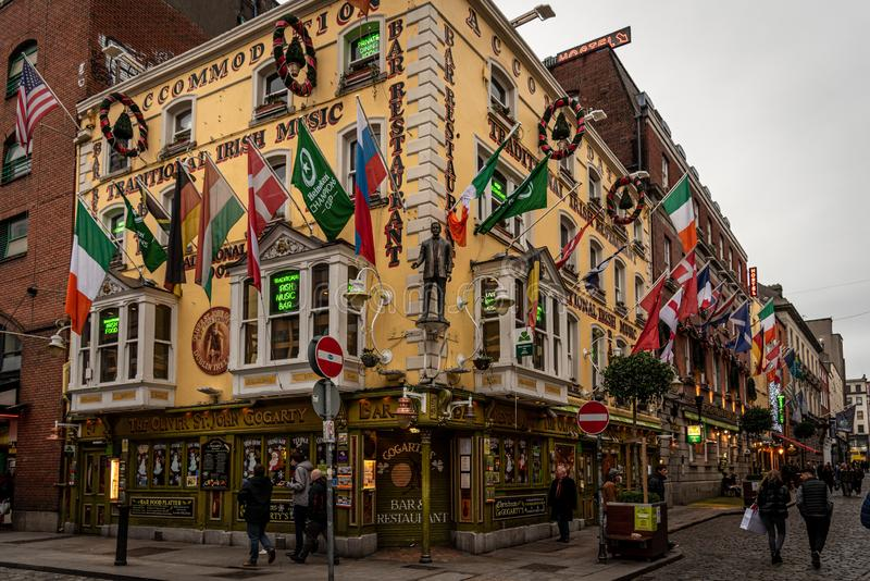 DUBLIN, IRELAND, DECEMBER 24, 2018: People walking in Temple Bar historic district, a cultural quarter with lively nightlife. Corner where Gogarty's bar royalty free stock photos