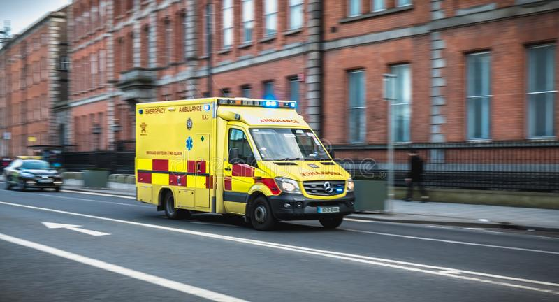 Irish ambulance driving fast on the streets of Dublin, Ireland. Dublin, Ireland - February 16, 2019: Irish ambulance driving fast on the streets of Dublin on a stock images