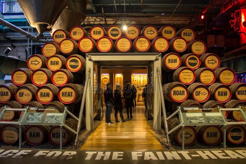 DUBLIN, IRELAND - FEBRUARY 7, 2017: People visiting the interior of the Guinness StoreHouse in Dublin. Wooden barrels of beer royalty free stock photography