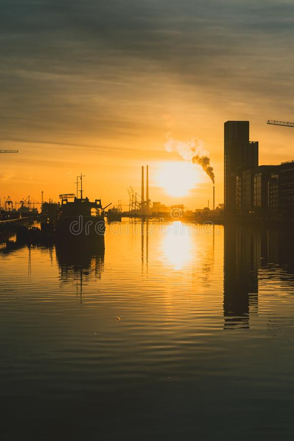 Gold toned sunrise over Dublin Bay and the docklands with cityscape including the Poolbeg Chimneys royalty free stock image