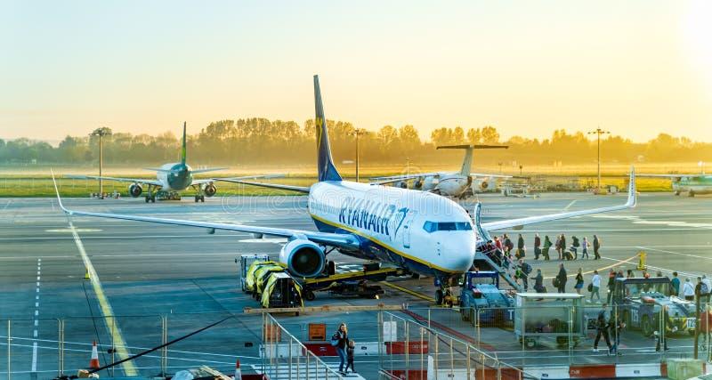 Dublin, Ireland, May 2019 Dublin airport, people boarding airplane, sunrise and early hour mist. Dublin, Ireland, May 2019 Dublin airport, people boarding stock photography