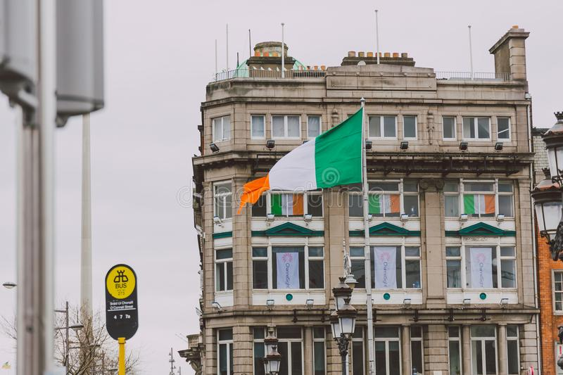 Buildings with Irish flags during the 2018 Saint Patrick`s parade in Dublin on O`Connell Bridge in the city centre stock images