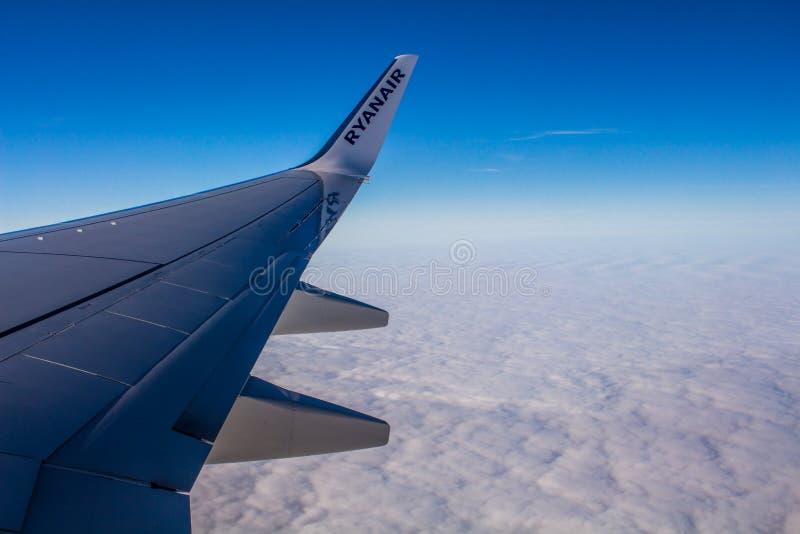 DUBLIN IRLAND - APRIL 23, 2017: Ryanair logo i vingen av flygplanet med himmel som bakgrunden Ryanair har billiga flyg royaltyfri foto