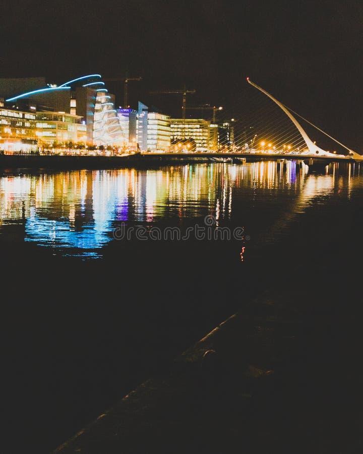 DUBLIN IRLAND - November 9th, 2018: nattetidskott av hamnkvarterbyggnaderna som reflekterar på floden Liffey i mitten av arkivbilder
