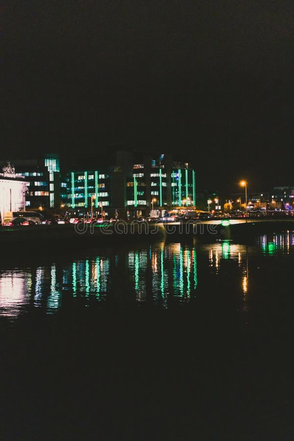 DUBLIN IRLAND - November 9th, 2018: nattetidskott av hamnkvarterbyggnaderna som reflekterar på floden Liffey i mitten av arkivfoton