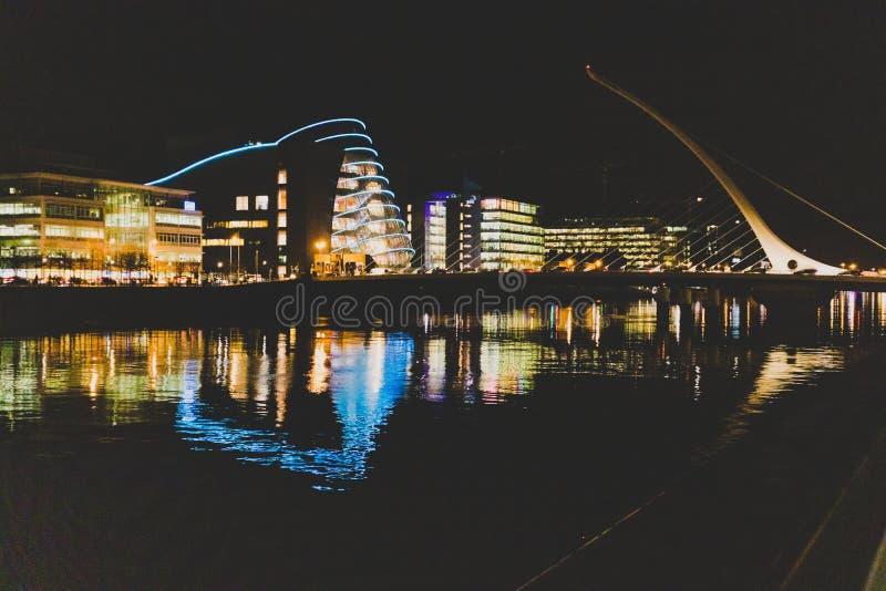 DUBLIN IRLAND - November 9th, 2018: nattetidskott av hamnkvarterbyggnaderna som reflekterar på floden Liffey i mitten av arkivfoto