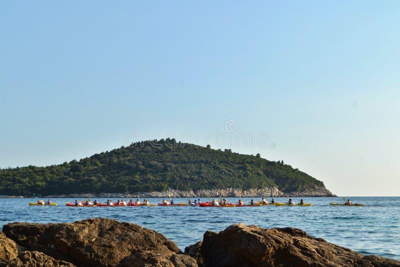 Dubrovnik/Croácia - 9 de setembro de 2014: O grupo de pessoas kayaking na baía de Dubrovnik imagens de stock royalty free
