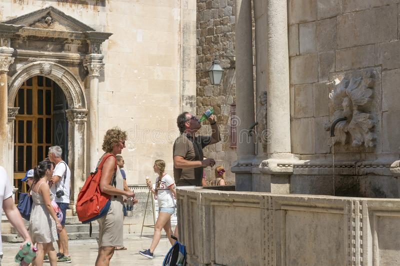 People quench their thirst near the fountain with water. Dubrovnik, Croatia - August 06, 2017: People quench their thirst near the fountain with water stock images