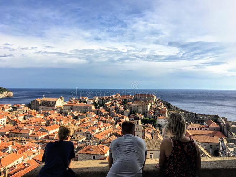 A group of friends atop the Walls of Dubrovnik admiring the old town of Dubrovnik stock photo