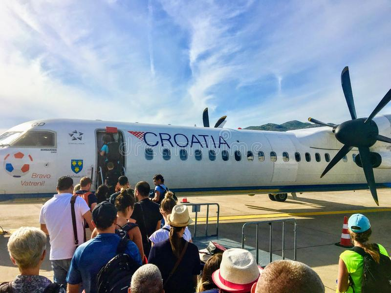 A group of passengers in line boarding a croatia airlines plane outside on the tarmac in Dubrovnik, Croatia. royalty free stock photography