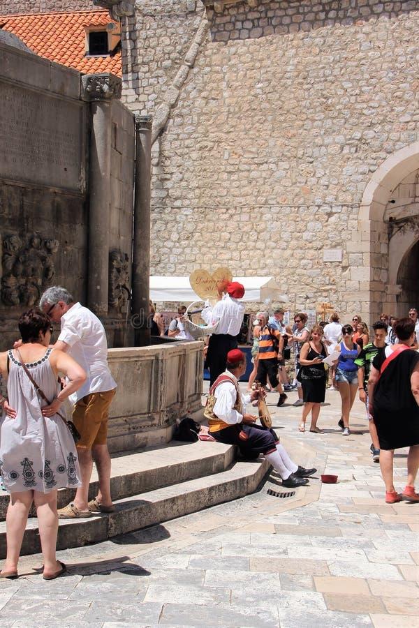 Dubrovnik, Croatie, juin 2015 Musicien de rue dans les vêtements et les touristes nationaux dans la place de la vieille ville photo libre de droits