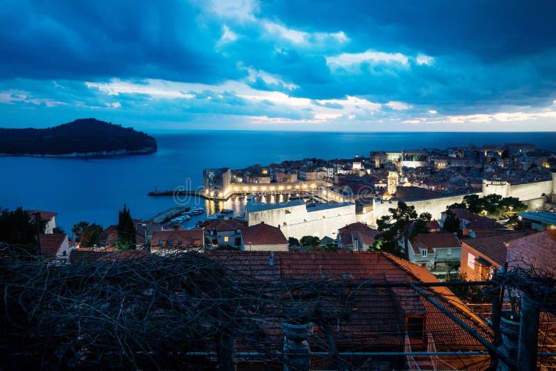 Dubrovnik flyg- nattsikt på gammal stad och port efter solnedgång med dramatisk cloudscape, Kroatien arkivfoton