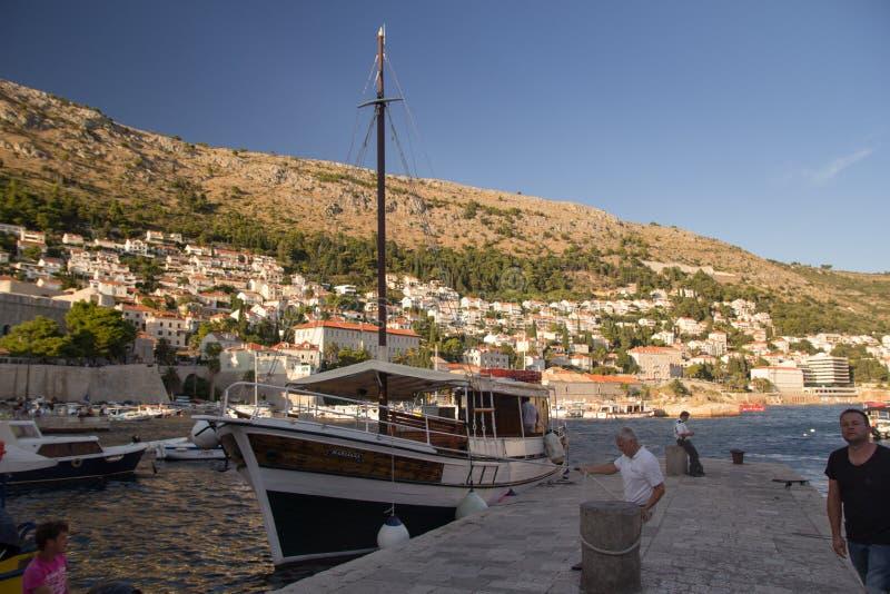 Dubrovnik Kroatien - 08 23 2016: En man förtöjde ett fartyg i porten av Dubrovnik royaltyfri bild