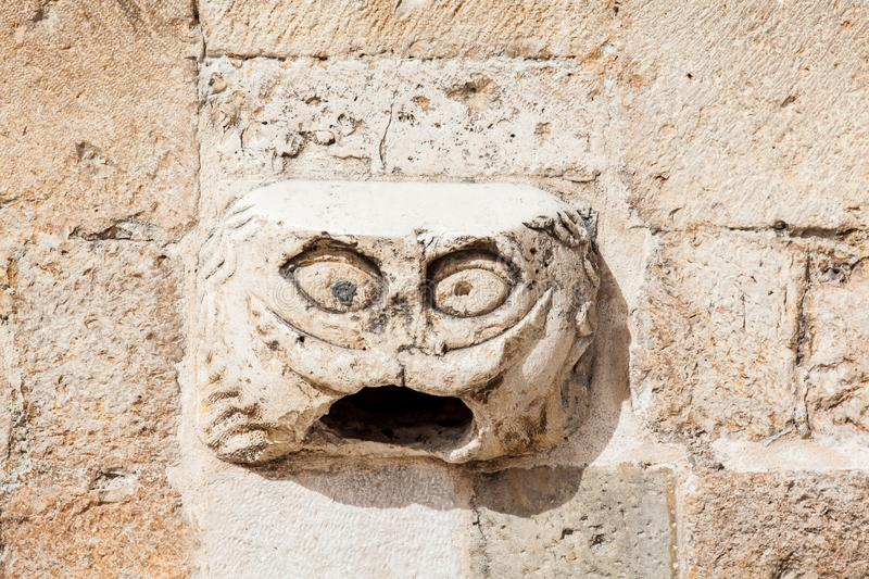 Dubrovnik Maskeron a Gargoyle head located next to the entrance to the Franciscan monastery. At Stradun street stock images