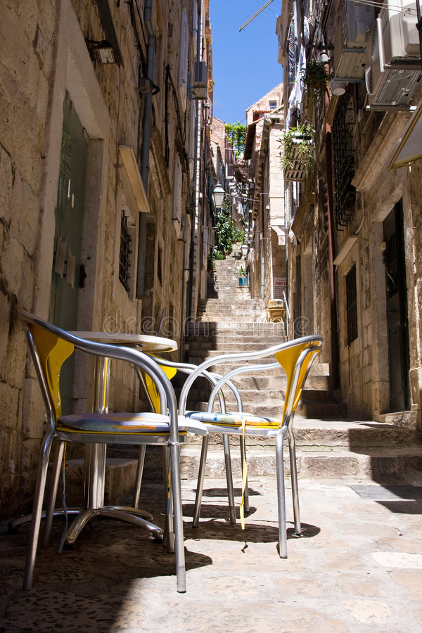 Dubrovnik street. A one narrow street in dubrovnik and one table with chairs for sitting stock photos