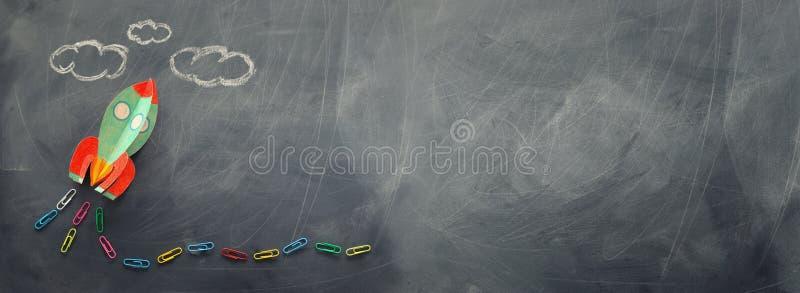 ?ducation De nouveau au concept d'?cole fusée coupée du papier et peinte au-dessus du fond de tableau noir Vue sup?rieure, config image libre de droits