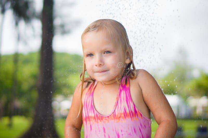 Ducha adorable de la toma de la muchacha debajo del árbol en el complejo playero tropical foto de archivo
