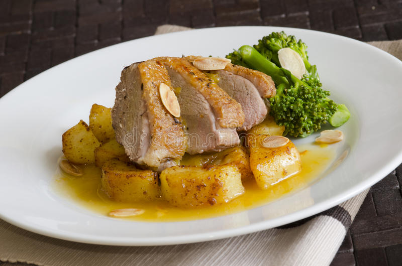 Duck breast fillets. Gressingham duck breast fillets with roasted potatoes and orange sauce stock image