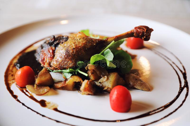 Duck confit , Roasted Duck leg French food. Duck confit on a dish in close up , Roasted Duck leg French food royalty free stock photo