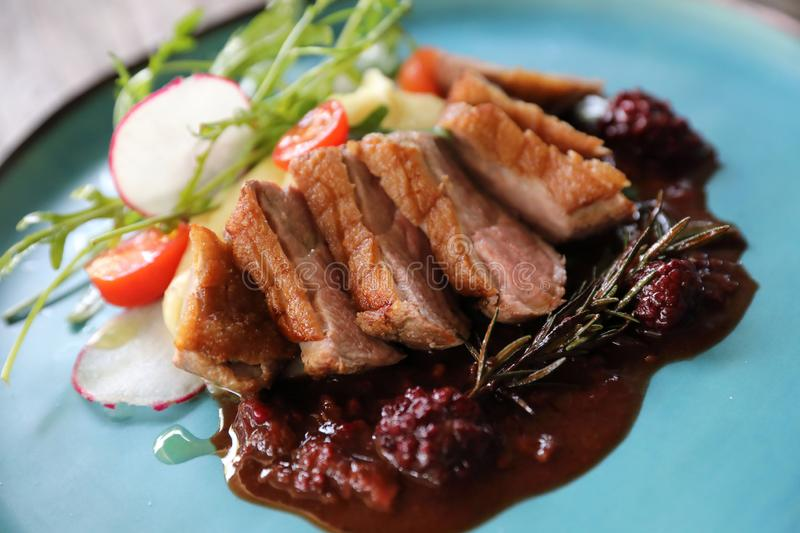 Duck confit with salad , baked apple and raspberry sauce served on wooden table stock photography