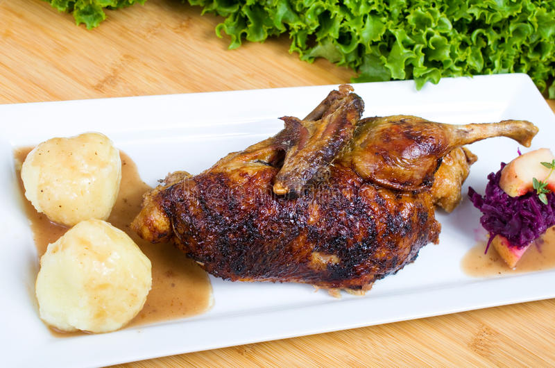 Duck with dumplings and red cabbage. Half roast duck with potato dumplings and red cabbage stock images