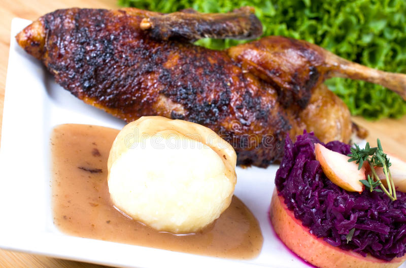 Duck with dumplings and red cabbage. Halved roasted duck with potato dumplings and red cabbage stock image