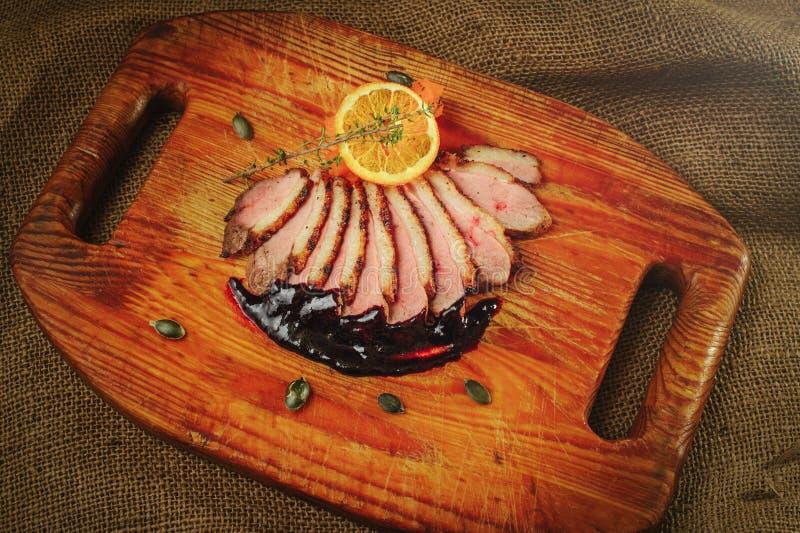 Duck a faixa em uma superfície de madeira com molho preto e alaranjado, alecrins e cenouras, ajuste acolhedor da tabela, saque do fotografia de stock royalty free