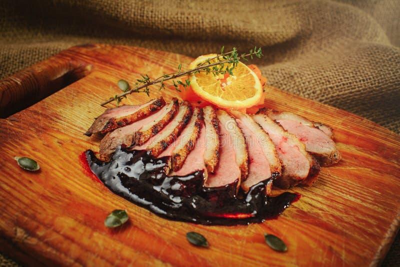 Duck a faixa em uma superfície de madeira com molho preto e alaranjado, alecrins e cenouras, ajuste acolhedor da tabela, saque do imagem de stock royalty free