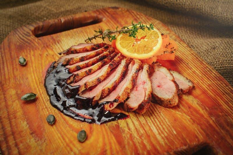 Duck a faixa em uma superfície de madeira com molho preto e alaranjado, alecrins e cenouras, ajuste acolhedor da tabela, saque do imagens de stock royalty free