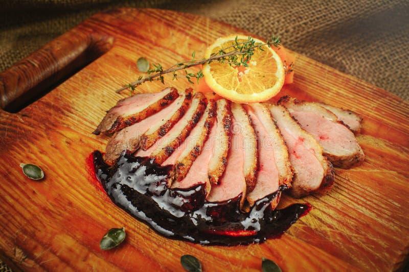 Duck a faixa em uma superfície de madeira com molho preto e alaranjado, alecrins e cenouras, ajuste acolhedor da tabela, saque do imagens de stock