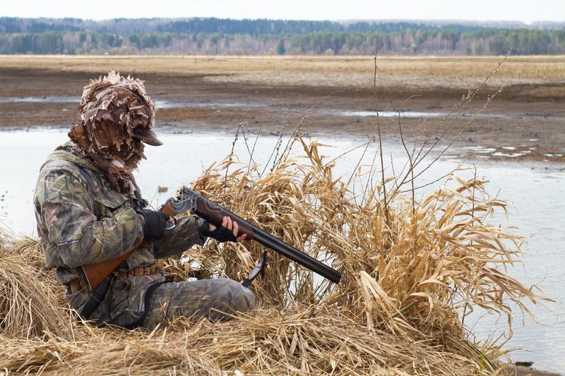 Duck hunter charges his shotgun next to the hunting blind stock image