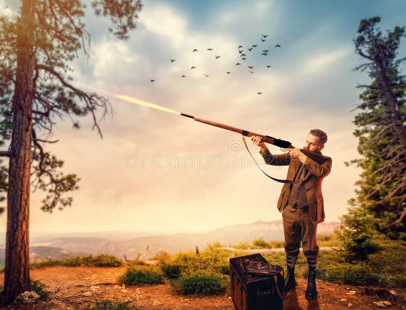 Duck hunter in hunting clothing aims an old rifle stock image