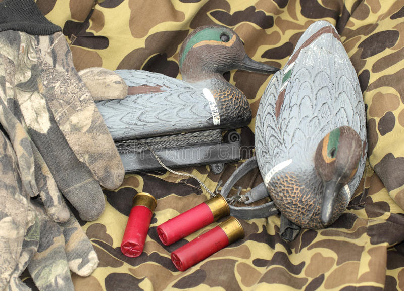 Duck hunter still life. Duck decoys with gloves and shotgun shells on camouflage background stock photography