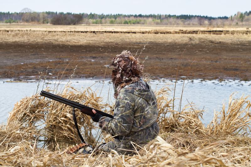 Duck hunting in camouflage sitting next to the lake. Duck hunting in camouflage with a shotgun sitting next to the lake during waterfowl hunting royalty free stock image
