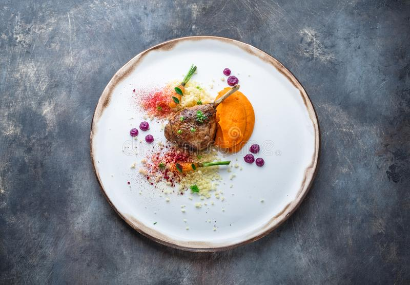 Duck leg confit with batat puree, carrots and couscous, restaurant meal.  royalty free stock images
