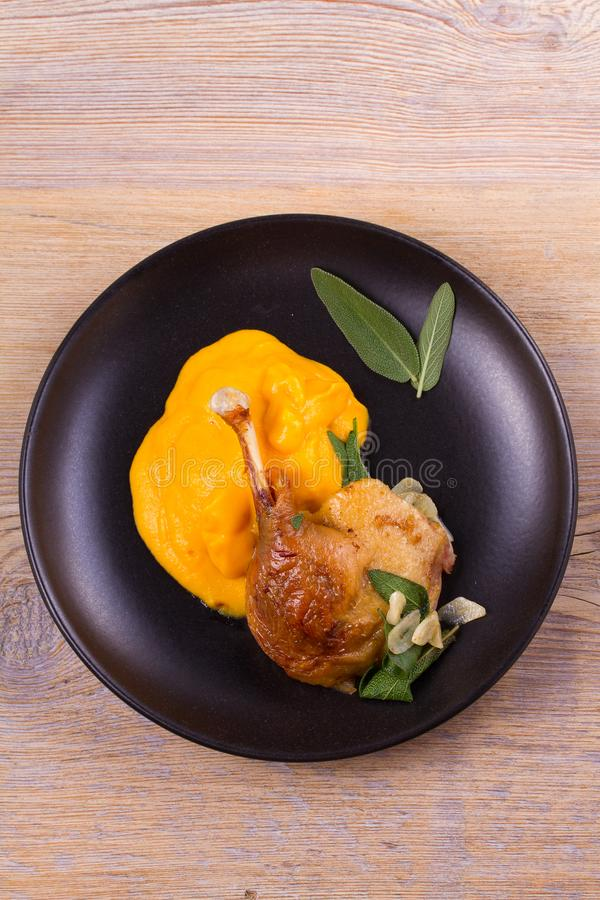 Duck leg with mashed sweet potato, sage and garlic in black plate on wooden background. stock photo