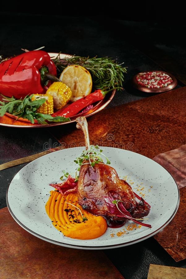 Duck leg with pumpkin puree, berry sauce and soy sprouts on a white plate on a copper background royalty free stock photography