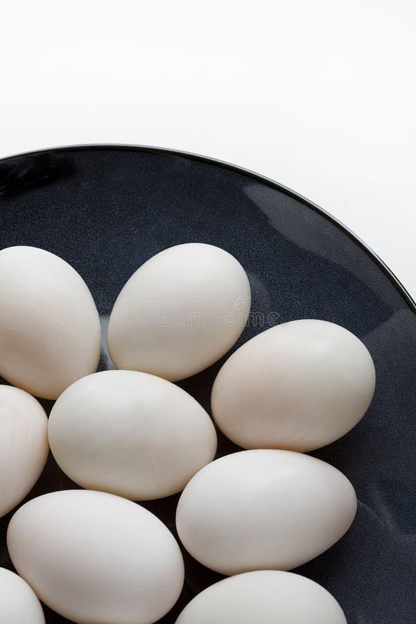 Duck los huevos en la placa azul en un fondo blanco imagen de archivo