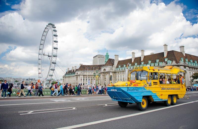 Duck o ônibus de excursão com o olho de Londres no fundo imagem de stock royalty free