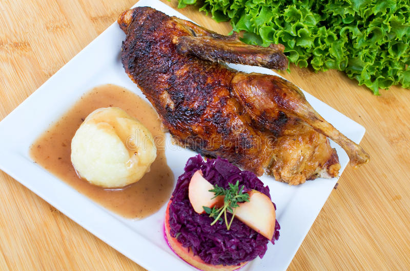 Duck with potato dumplings and red cabbage. Halved roasted duck with potato dumplings and red cabbage stock photos