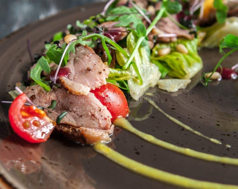 Duck Salad mit Arugula-Gemüse, Kiefern-Nüssen und orange Soße Die Ansicht von der Spitze auf einem dunklen hölzernen Hintergrund stockfotografie
