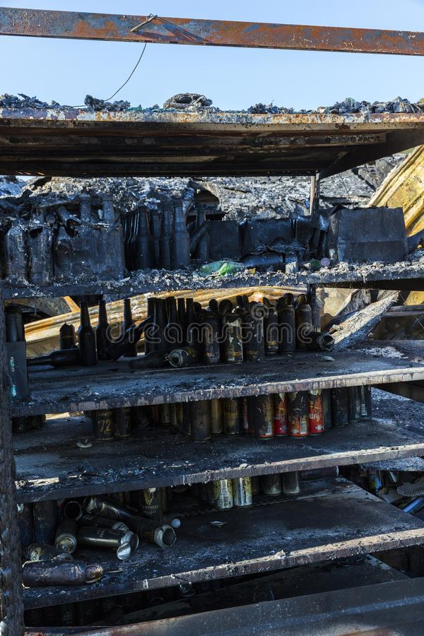 DUCLAIR, FRANCE - OCTOBER Circa, 2018 : Damaged CARREFOUR MARKET supermarket after arson fire with burn debris of can beer brand stock photography