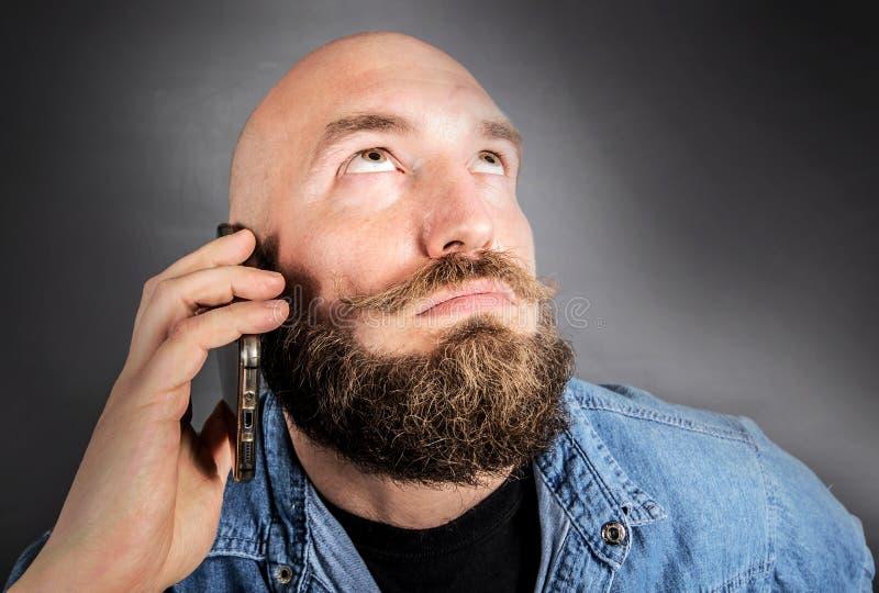 Dudar al hombre que habla en el teléfono imágenes de archivo libres de regalías