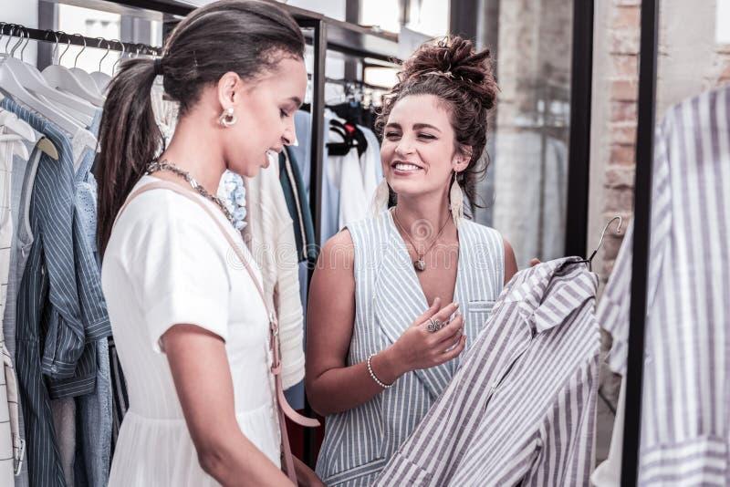 Dueño alegre del boutique de la moda que recomienda el vestido agradable su visitante fotografía de archivo libre de regalías